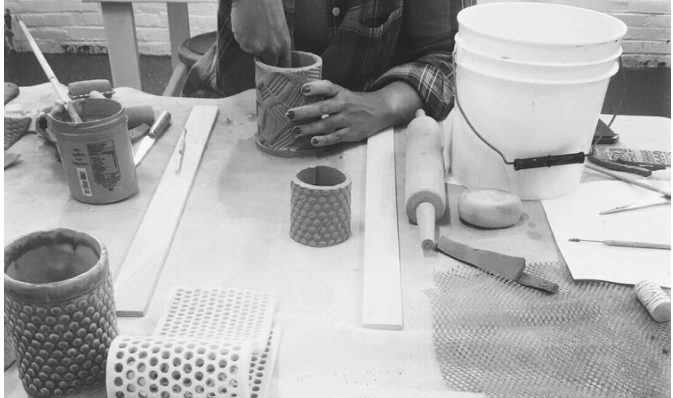 A Black person working clay on a table of tools