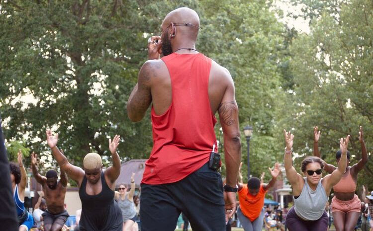 a Black man in a red tank top leading his community in a pilates class outdoors